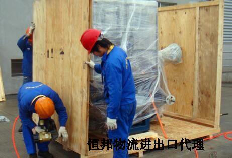 工人对木工机床打木箱包装